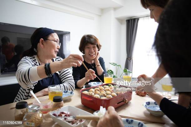 japanese senior woman having home party - takoyaki stock pictures, royalty-free photos & images