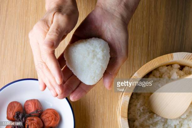japanese senior woman holding rice ball and rice cooked with umeboshi - rice ball stock pictures, royalty-free photos & images