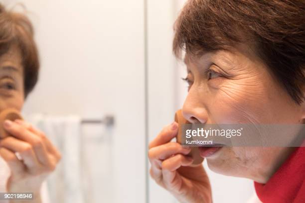 日本の年配の女性をことを置くこと - 美容 ストックフォトと画像
