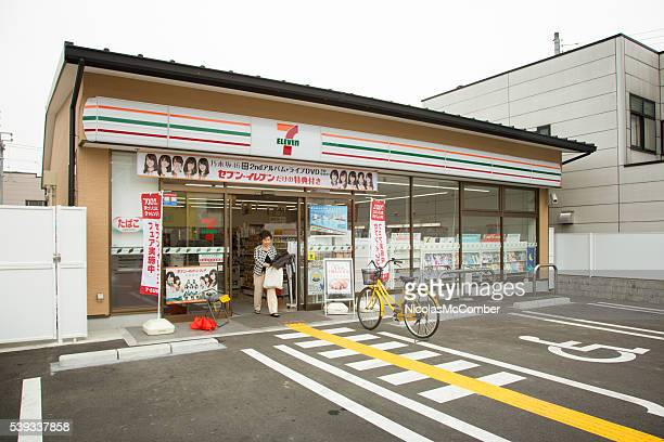 japanese seven eleven convenience store with customer walking out - convenience store stock photos and pictures