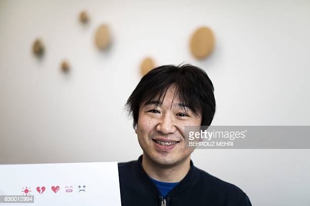 Japanese Shigetaka Kurita the man who created emoji charachters gestures next to the emoji charachters during an interview with AFP in Tokyo on...