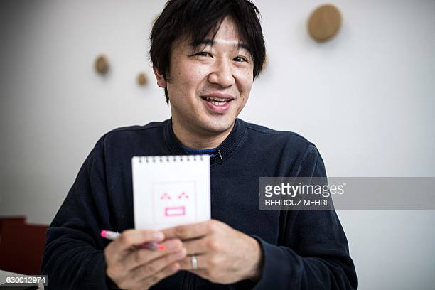 Japanese Shigetaka Kurita the man who created emoji charachters shows an emoji charachter after drawing during an interview with AFP in Tokyo on...