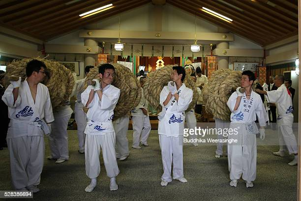 Japanese Shinto shrine priests carry the Shimenawa Sacred ropes for hang to between God Married Stones during the Oshimenawahari ceremony of Meotoiwa...