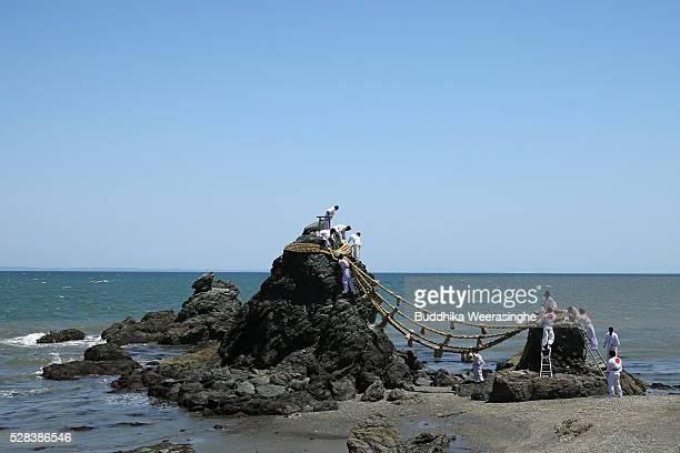 Japanese Shinto shrine priests hang the shimenawa or the sacred ropes between the Meotoiwa or the sacred Couple Rock during the Oshimenawahari...