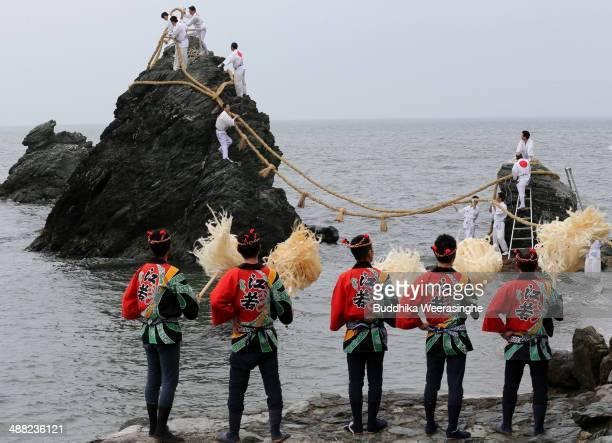 Japanese Shinto shrine priests hang the Shimenawa, Sacred ropes between God Married Stones during the Oshimenawahari ceremony of Meoto-iwa or the...
