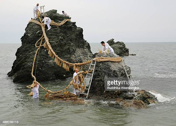 Japanese Shinto shrine priests remove the old Shimenawa Sacred ropeswhich hang between God Married Stones during the Oshimenawahari ceremony of...