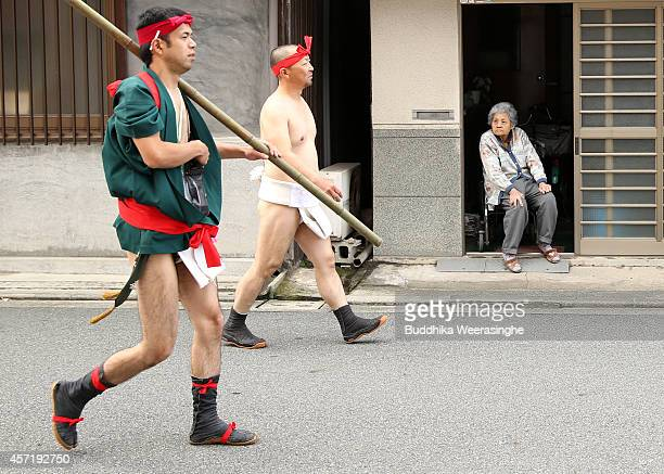 Japanese Shrine Parishioners of Matsubara team wears Fundoshi or loincloths as they walk past an elderly woman during the first day of the Nada...