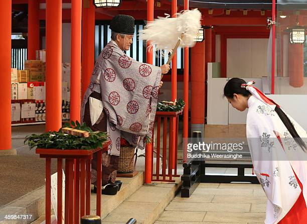 Japanese Shrine priest blesses to mark New Year's day as Miko bows the head during the celebration of 'Year of the Horse' at Ikuta Shrine on January...