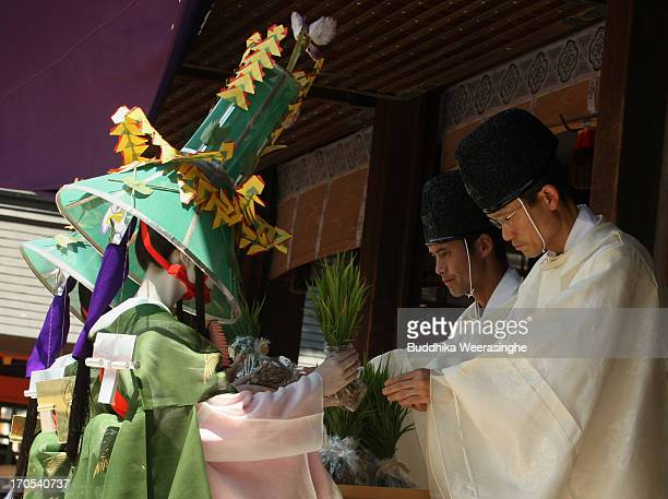 Japanese shrine priests hand over sacred rice seed to women in traditional costumes during the Otaue Shinji sacred rice planting annual ceremony at...