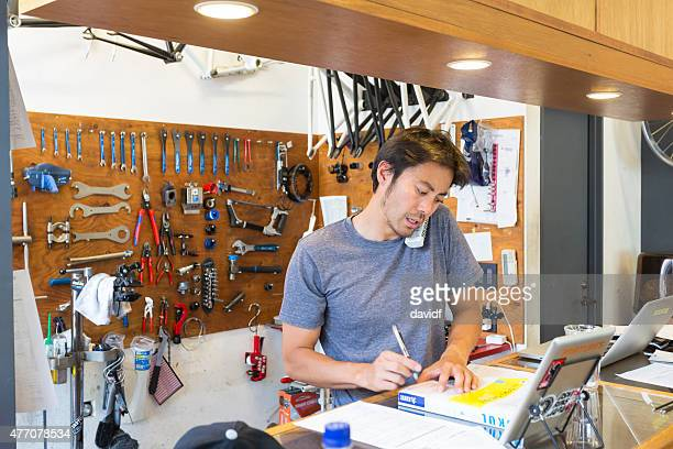 Japanese Small Businessman on the Phone in a Bike Shop