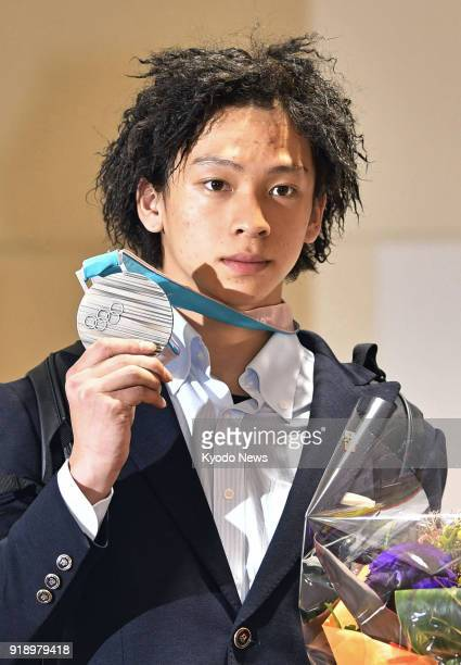 Japanese snowboarder Ayumu Hirano shows off his silver medal for the men's halfpipe event at the Pyeongchang Winter Olympics in South Korea upon his...
