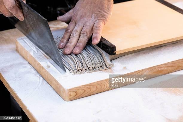 日本そば専門の職人によって作られました。そば粉に水を入れ、麺棒で生地を伸ばす、それを包丁で切る。 - 蕎麦 ストックフォトと画像