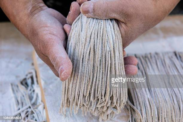japanese soba made by professional craftsmen. put the water in buckwheat flour, stretch the dough with a noodle stick and cut it up with a kitchen knife. - soba stock pictures, royalty-free photos & images