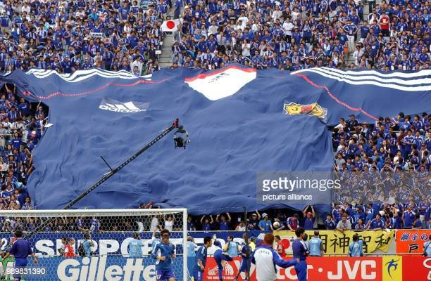 Japanese soccer fans unfold a gigantic jersey of the Japanese national soccer team during the 2002 World Cup group game between Japan and Belgium in...
