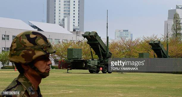 A Japanese soldier walks past Patriot Advanced Capability3 missile launchers deployed at the Defence Ministry in Tokyo on April 10 2013 Japan is on...