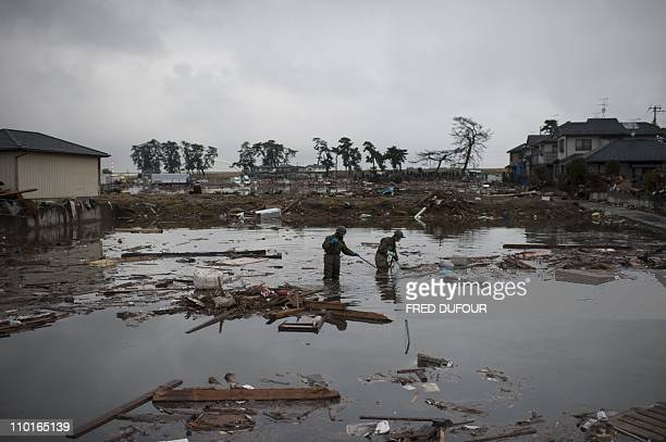 Japanese soldiers check for dead bodies in the water in Sendai Miyagi prefecture on March 16 2011 days after a massive earthquake and tsunami...