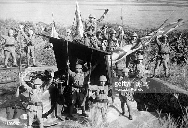 Japanese soldiers cheering beside an enemy coastal artillery position after having defeated the British troops Hong Kong December 1941
