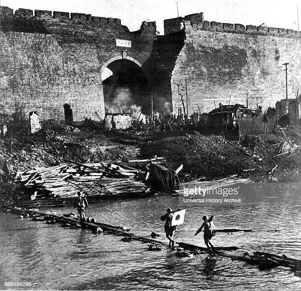Japanese soldiers crossing a river near Nanjing City wall China 1937