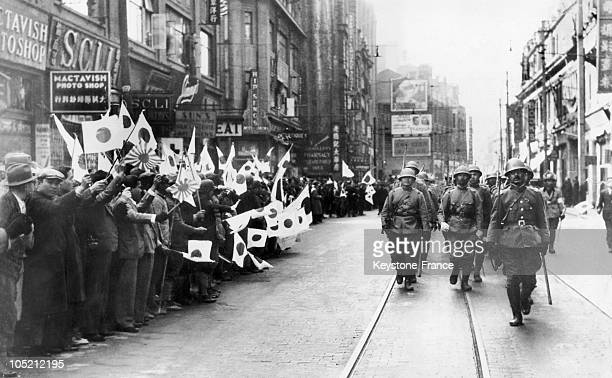 Japanese Soldiers Filing Through The Streets Of Shanghai Conquered By Japan In 1937 They Are Greeted By The Chinese Population Waving Japanese Flags...