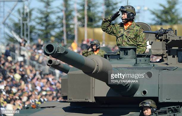 Japanese soldiers salute from their tanks during the military review at the Ground SelfDefence Force's Asaka training ground on October 27 2013...