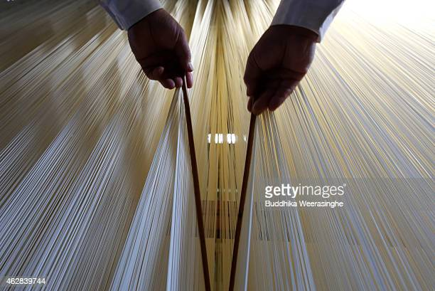 Japanese somen maker uses chopsticks to stretch drying Ibonoito somen noodles on February 6 2015 in Tatsuno Japan Somen is a type of Japanse wheat...