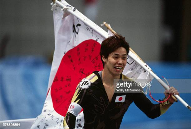 Japanese speed skater Hiroyasu Shimizu carries his countries flag after winning the gold medal in the men's 500m at M-Wave during the 1998 Winter...