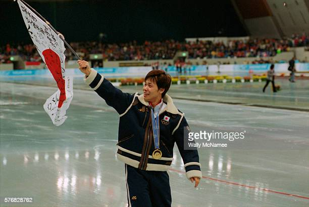 Japanese speed skater Hiroyasu Shimizu carries his country's flag after winning the gold medal in the men's 500m at MWave during the 1998 Winter...