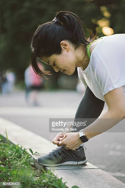 Japanese sport woman tying her shoelaces during daily workout