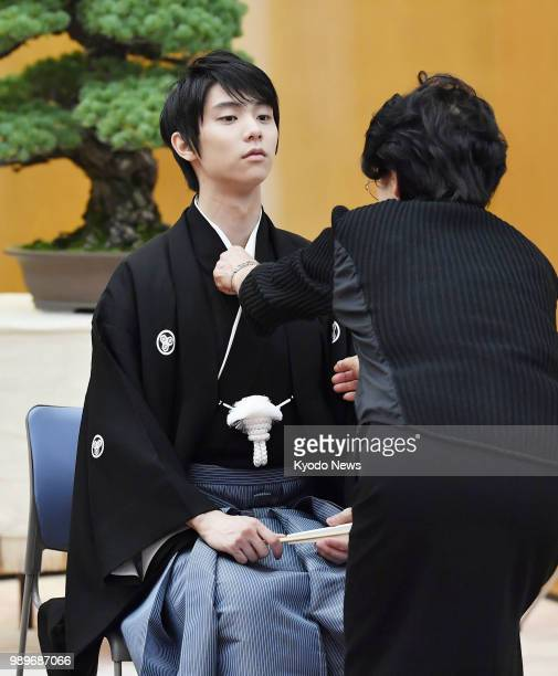 Japanese star figure skater Yuzuru Hanyu wearing a special type of 'hakama' skirt originated in his hometown Sendai has his kimono fixed while...