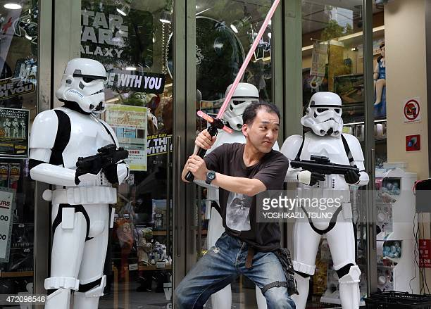 Japanese Star Wars fan Motoi Takemura poses with Storm Troopers at a toy shop in Tokyo on May 4 2015 May 4th is called the 'Star Wars Day' among Star...