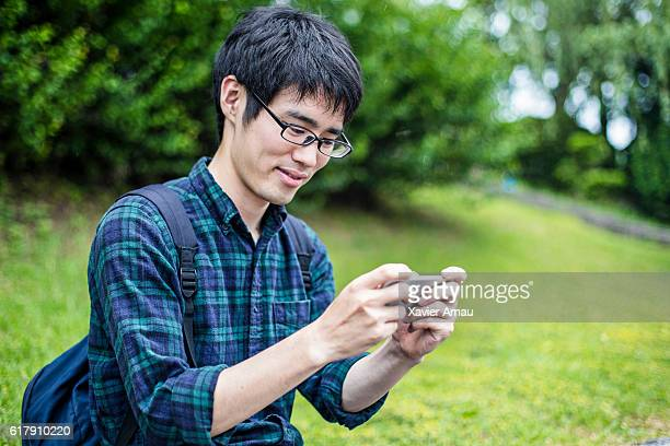 japanese student using mobile phone in campus - leisure games ストックフォトと画像