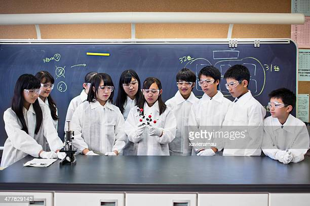 Japanese students examining a molecular model at the science class