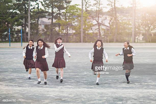japanese students girls running in the school playground - cute highschool girls stock photos and pictures