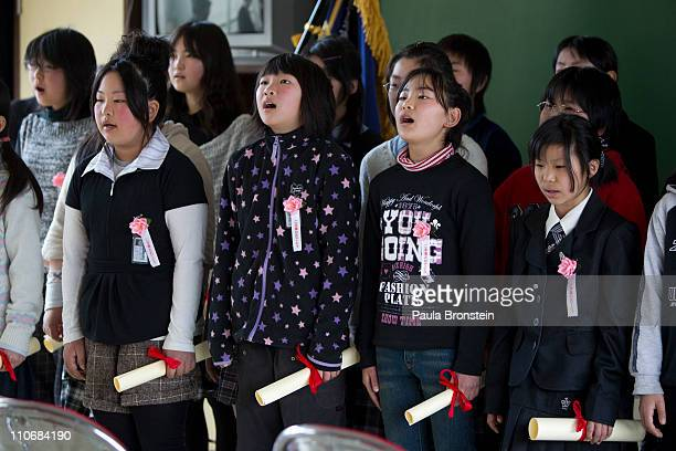 Japanese students sing during a graduation ceremony for the sixth grade at the Ohya Elementary school March 23 2011 in Kesennuma Miyagi Japan Twelve...