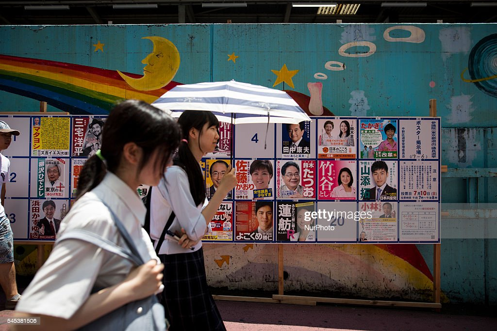 Japanese students walks past at campaign posters with pictures of candidates for the 2016 Upper House election in Tokyo, Japan on Thursday, July 7, 2016. The July 10 Upper house election is the first nation-wide election in Japan after government law changes its voting age from 20 years old to 18 years old.