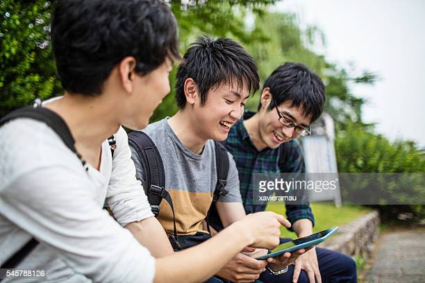 Japanese students working  together with a digital tablet