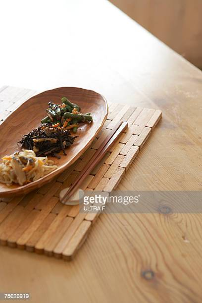 Japanese style vegetables in wooden tray with chopsticks on wooden table