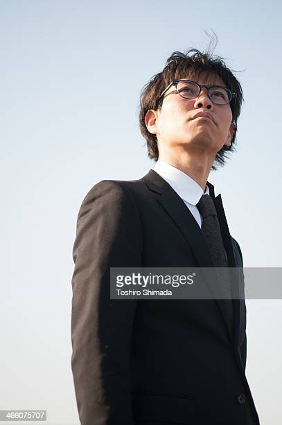 Japanese suited man looking up