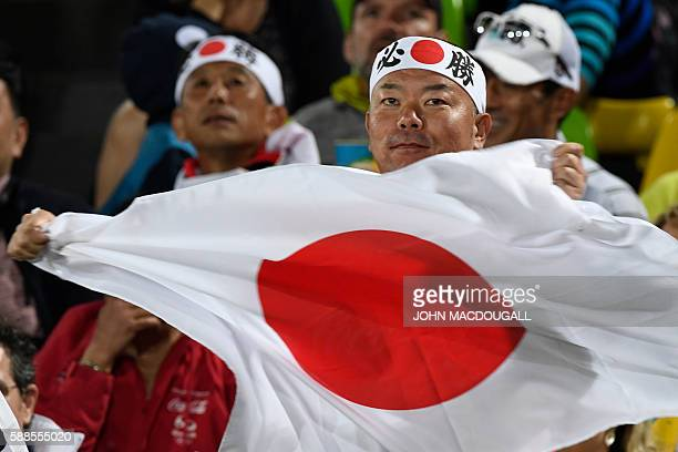 A Japanese supporter holds a national flag before the mens rugby sevens bronze medal match between Japan and South Africa during the Rio 2016 Olympic...