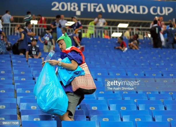 Japanese supporters clean the stand after their team's 23 defeat in the 2018 FIFA World Cup Russia Round of 16 match between Belgium and Japan at...