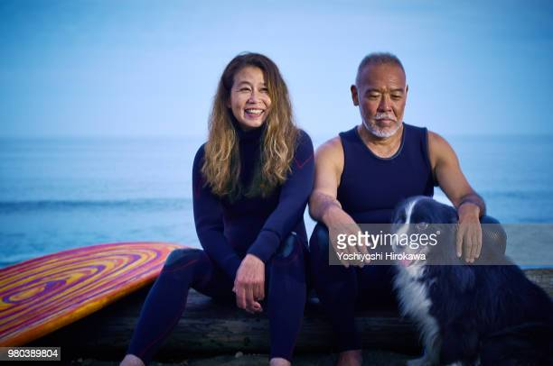 Japanese surfer family sitting with dog at early morning