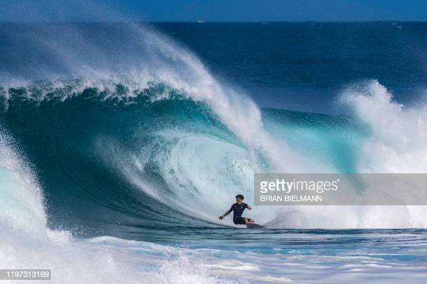 Japanese surfer rides a wave ahead of the Volcom Pipe Pro at Backdoor Pipeline on the north shore of Oahu in Hawaii on January 28, 2020. / RESTRICTED...