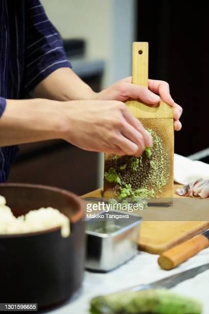 a japanese sushi chef grating fresh wasabi - wasabi sauce stock pictures, royalty-free photos & images