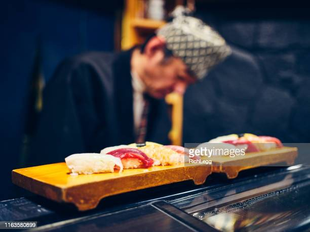 japanese sushi chef in a sushi shop - nigiri stock pictures, royalty-free photos & images