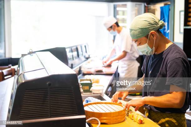 japanese sushi chefs wearing a masks for covid-19 - catering building stock pictures, royalty-free photos & images