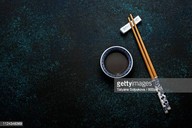 japanese sushi chopsticks and soy sauce bowl on blue dark stone background - ワサビ ストックフォトと画像