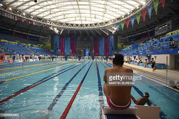 A Japanese swimmer sits on a starting block during a practice session at the Munhak Park Taehwan Aquatics Center for the 2014 Asian Games in Incheon...