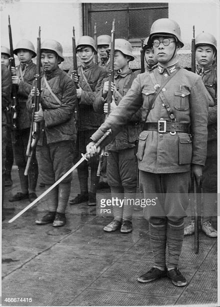 Japanese TaTao troops criminals and youngsters making up an untrained military in formation behind an officer with a Samurai sword World War Two...