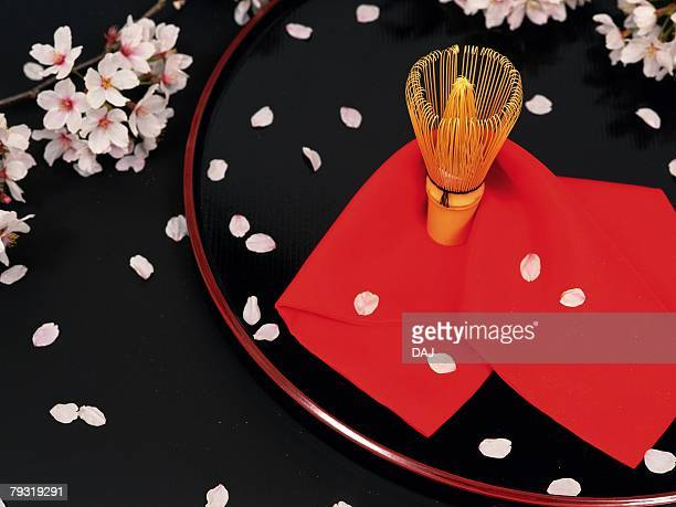 A Japanese tea whisk and cherry blossom petals, High Angle View