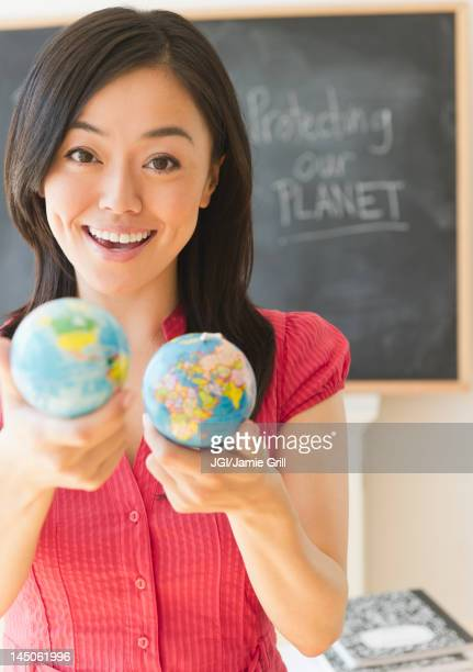 Japanese teacher holding small globes in classroom